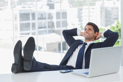 Επιτυχής χαλάρωση επιχειρηματιών με τα πόδια του στο γραφείο του Στοκ φωτογραφίες με δικαίωμα ελεύθερης χρήσης