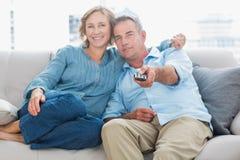 愉快的夫妇拥抱和坐看电视的长沙发 免版税图库摄影