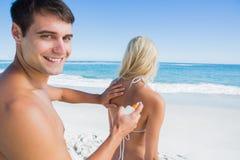 供以人员把太阳奶油放在微笑对照相机的女朋友上 免版税库存照片