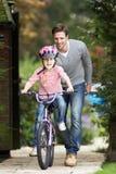 骑自行车的父亲教的女儿在庭院里 免版税库存图片