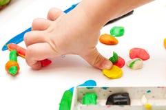 有彩色塑泥的婴孩手 库存图片