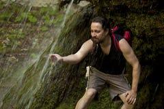 在瀑布下的远足者 免版税库存图片