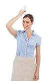 拿着在她的头上的女实业家一个电灯泡 免版税库存照片