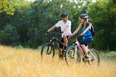 Νέα ευτυχή ποδήλατα βουνών ζεύγους οδηγώντας υπαίθρια Στοκ εικόνα με δικαίωμα ελεύθερης χρήσης