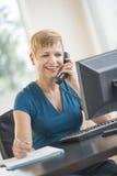 使用电话的愉快的女实业家在书桌 库存照片