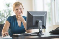 坐在计算机书桌的愉快的女实业家 库存图片
