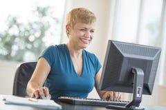 使用计算机的愉快的女实业家在书桌 免版税库存图片