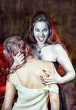 美丽的吸血鬼和她的受害者 免版税库存照片