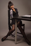 一套黑衣服的妇女坐办公室桌 免版税库存照片