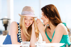 女孩说闲话在海滩的咖啡馆 库存照片