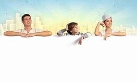 与空白的横幅的愉快的年轻家庭 免版税库存照片