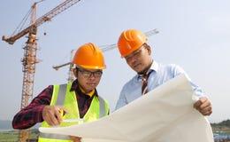 在建造场所前面的年轻建筑师讨论 图库摄影