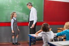 Δάσκαλος και κορίτσι που συζητούν το μάθημα στην τάξη Στοκ Φωτογραφία