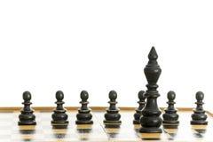 Черные король и пешки на шахматной доске Стоковые Изображения