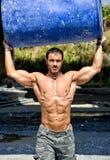 热,肌肉建筑工人赤裸上身的运载的桶 库存图片