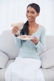 微笑的可爱的妇女坐吃三明治的舒适沙发 图库摄影