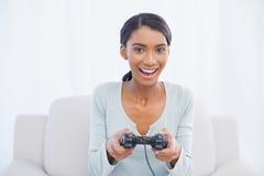 微笑的妇女坐打电子游戏的沙发 库存照片
