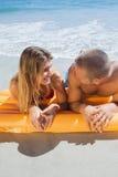 在看彼此的泳装的愉快的逗人喜爱的夫妇 图库摄影