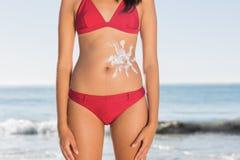 有太阳奶油的亭亭玉立的妇女身体在腹部 免版税库存照片