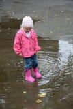 站立在水坑的女孩 免版税图库摄影
