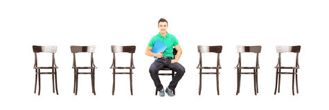 在椅子和等待的工作面试的年轻男性开会 免版税库存图片