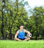 年轻微笑的男性运动员下来坐与球的一棵草 免版税图库摄影