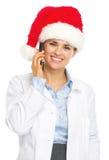 圣诞老人帽子谈的手机的微笑的医生妇女 免版税库存图片