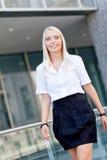 站立可爱的年轻成功的微笑的女商人室外 免版税图库摄影