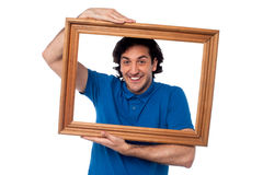 拿着木画框的人 免版税库存图片