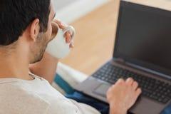 英俊的棕色毛发的人饮用的咖啡,当使用他的膝上型计算机时 免版税库存图片