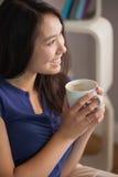 愉快的亚裔妇女坐拿着杯子咖啡厕所的长沙发 免版税库存照片