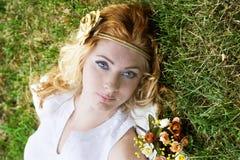 说谎在绿草的红发妇女 免版税库存照片