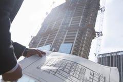 拿着大厦在建造场所,中央部位的图纸建筑师 图库摄影
