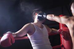 在的男性拳击手投掷在拳击台的肩膀观点一个出坯杆 免版税库存照片