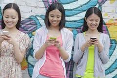 三站立并行和发短信在他们的在墙壁前面的电话的微笑的少妇有街道画的 免版税库存照片