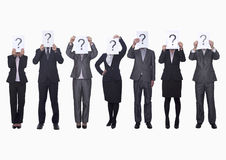 Средств группа в составе бизнесмены в ряд задерживая бумагу с вопросительным знаком, затемненной стороной, съемкой студии Стоковое Изображение RF