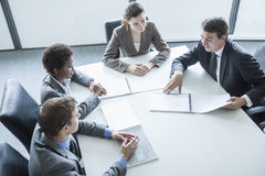 开四个的商人坐在桌附近和业务会议,大角度看法 免版税库存图片