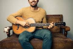 弹在老沙发的愉快的年轻人吉他 图库摄影