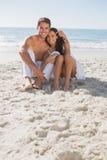 微笑对照相机的拥抱的夫妇坐沙子 图库摄影
