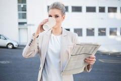 严肃的时髦的女实业家饮用的咖啡 库存图片