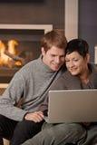 使用膝上型计算机的夫妇在冬天 图库摄影