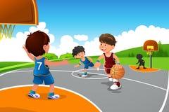 打篮球的孩子在操场 免版税库存照片
