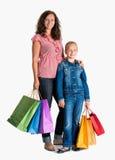 微笑的母亲和女儿有购物袋的 免版税库存照片