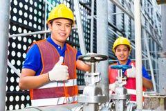 工作在阀门的亚裔技术员或工程师 免版税库存照片