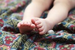 在一条五颜六色的床罩的婴孩脚有几何样式的 免版税图库摄影