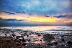 在一个多岩石的海滩的剧烈的日出。波罗的海 免版税库存照片