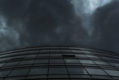 在雨云下的曲线玻璃大厦门面 免版税库存照片