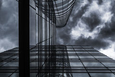 高层玻璃大厦在雨云天空下 免版税库存图片
