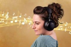 有耳机的少妇听到音乐的 免版税库存图片