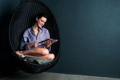 泡影椅子读书杂志的俏丽的妇女 免版税库存图片